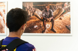 Visitante do MAUC olhando uma das obras de arte expostas no museu