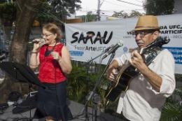 Imagem: Foto de servidor com violão ao lado de servidora cantando no palco do 1° Sarau FazerArte